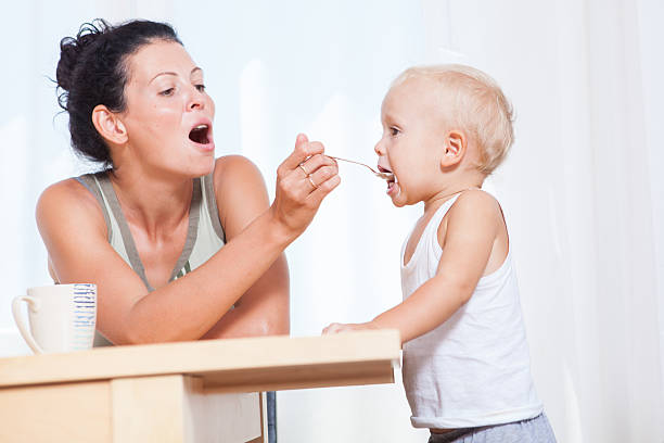 Beautiful young mother feeding with breakfast her little son stock photo