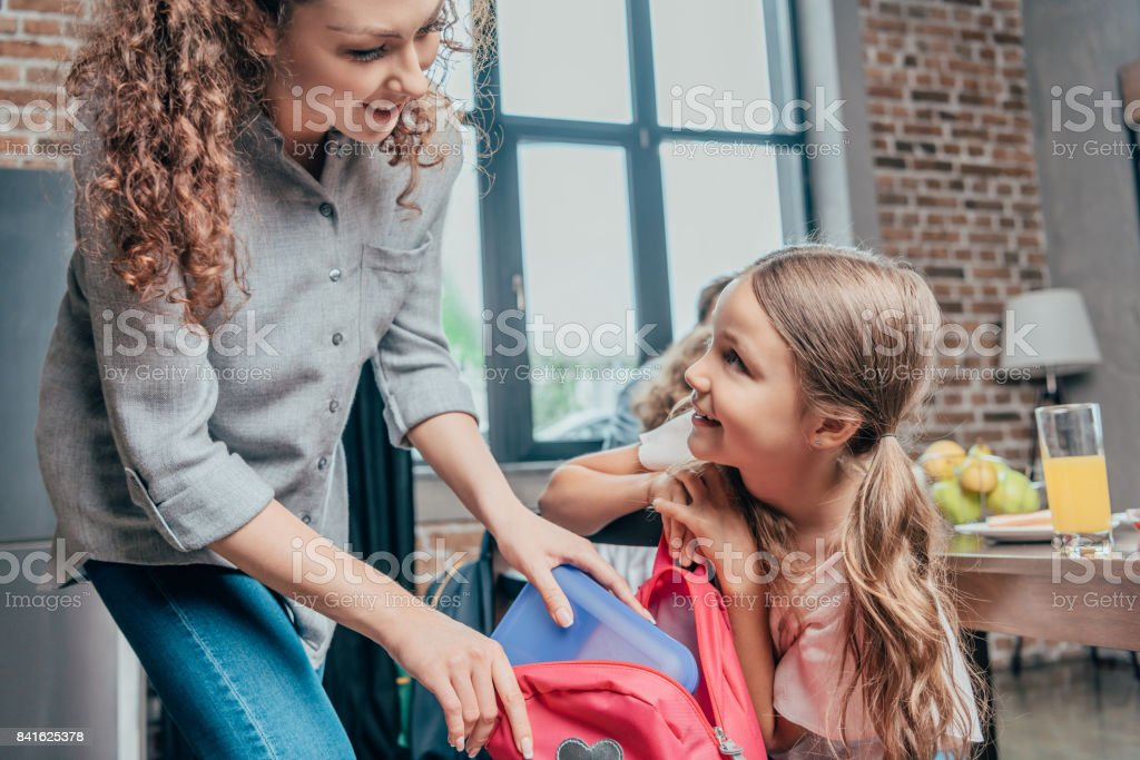 beautiful young mother giving school lunch to daughter stock photo