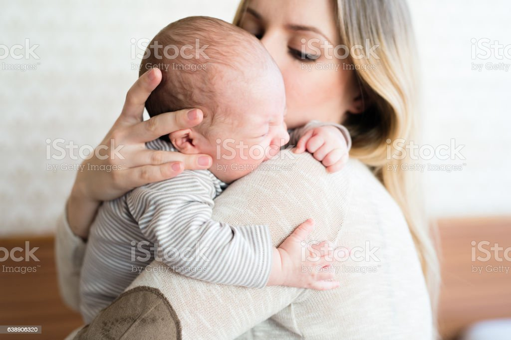 Beautiful young mother holding baby son in her arms - foto de acervo