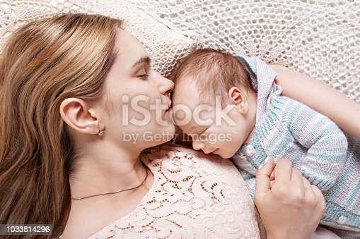 istock Beautiful young mother kissing and hugging her newborn baby boy. Motherhood concept. Happy family concept 1033814296