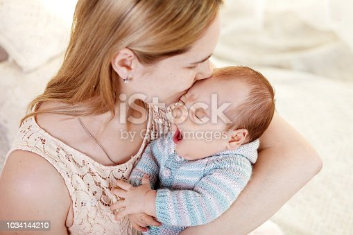 909771884 istock photo Beautiful young mother kissing and hugging her newborn baby boy. Motherhood concept. Happy family concept 1034144210