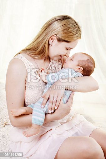 909771884 istock photo Beautiful young mother kissing and hugging her newborn baby boy. Motherhood concept. Happy family concept 1034144258