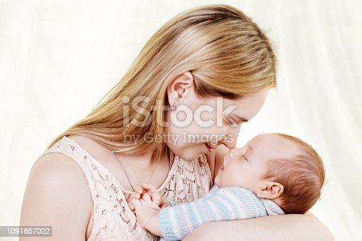 909771884 istock photo Beautiful young mother kissing and hugging her newborn baby boy. Motherhood concept. Happy family concept 1091857022