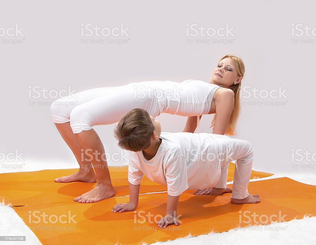 Beautiful young mother practices yoga with her son royalty-free stock photo