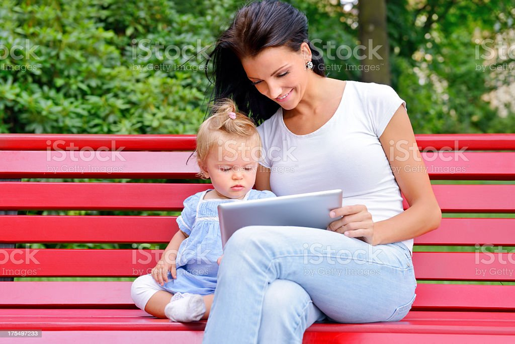 Beautiful young mother with her baby girl using digital tablet royalty-free stock photo