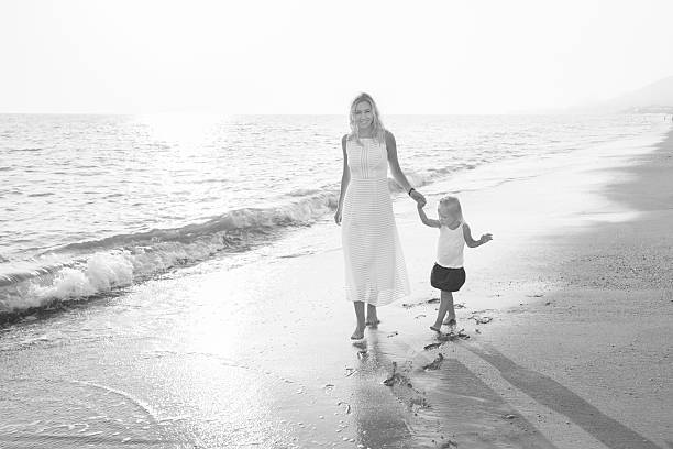 Beautiful young mother with her daughter walking on the beach stock photo