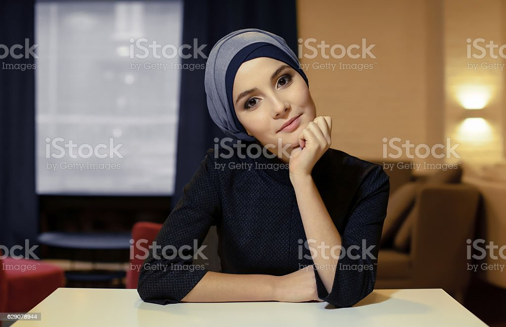 beautiful young Muslim woman sitting at a table stock photo