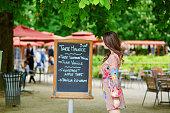 istock Beautiful young Parisian woman reading menu 504985366