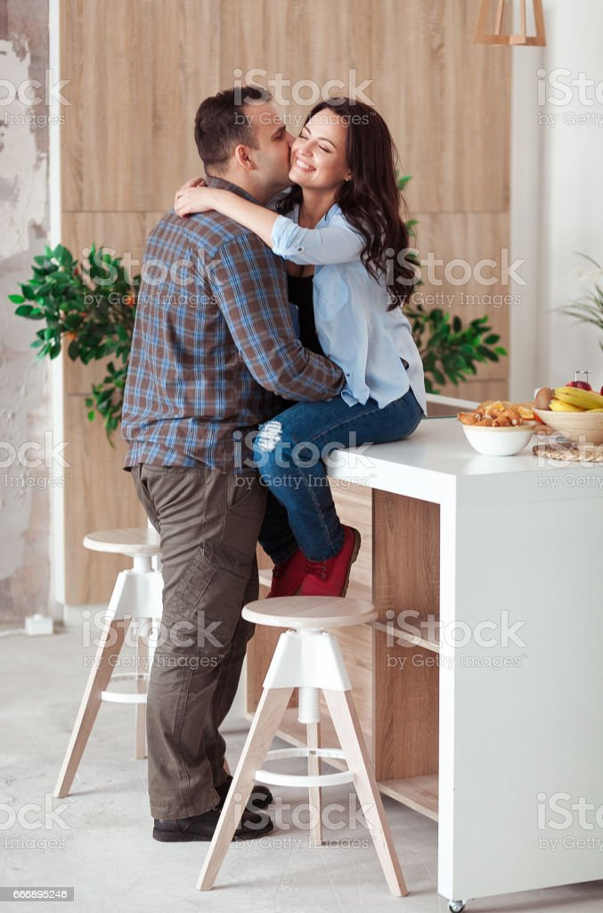Beautiful Young Passionate Couple Is Smiling And Hugging Before Having Sex In Kitchen At Home Royalty