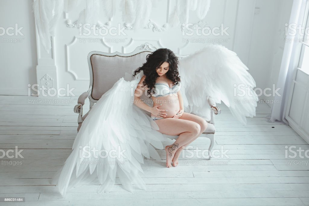 Beautiful Young Pregnant Girl With Big Angel Wings In White Studio