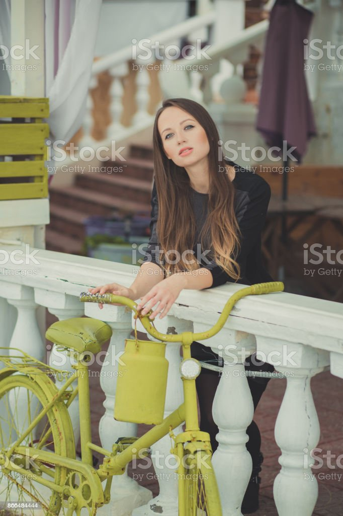 Beautiful young pregnant lady woman with brunette hair and green eyes lonely dreaming close to bicycle in autumn city looking to camera portrait stock photo