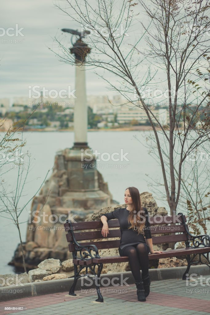 Beautiful young pregnant lady woman with brunette hair lonely dreaming sitting on wooden beanch in waterfront autumn city with amazing monument on background stock photo