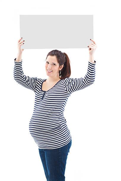 schöne junge schwangere frau hält ein schild - sprüche zur schwangerschaft stock-fotos und bilder