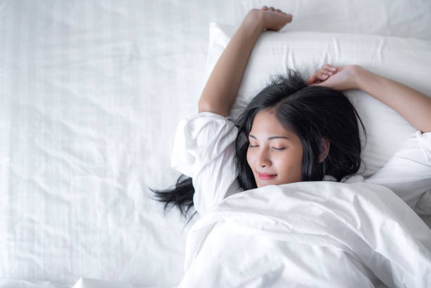beautiful young pretty asian woman wake up and make happy smile with white shirt at the white bed in the morning. - łóżko zdjęcia i obrazy z banku zdjęć