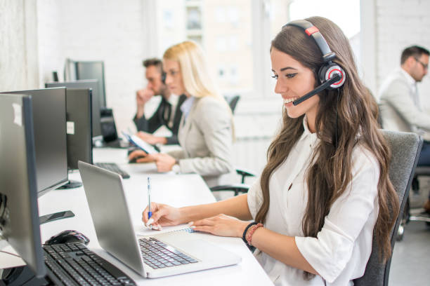 Beautiful young pretty woman with hands-free headset copying some data from laptop to her notepad in office. stock photo