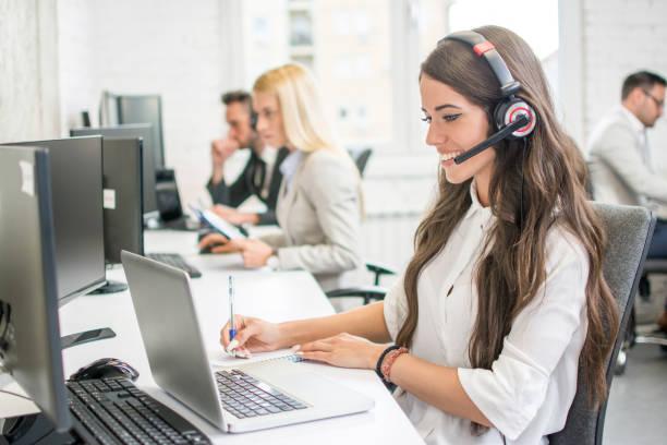 Schöne junge hübsche Frau mit Freisprech-Headset kopieren einige Daten vom Laptop auf ihren Notizblock im Büro. – Foto