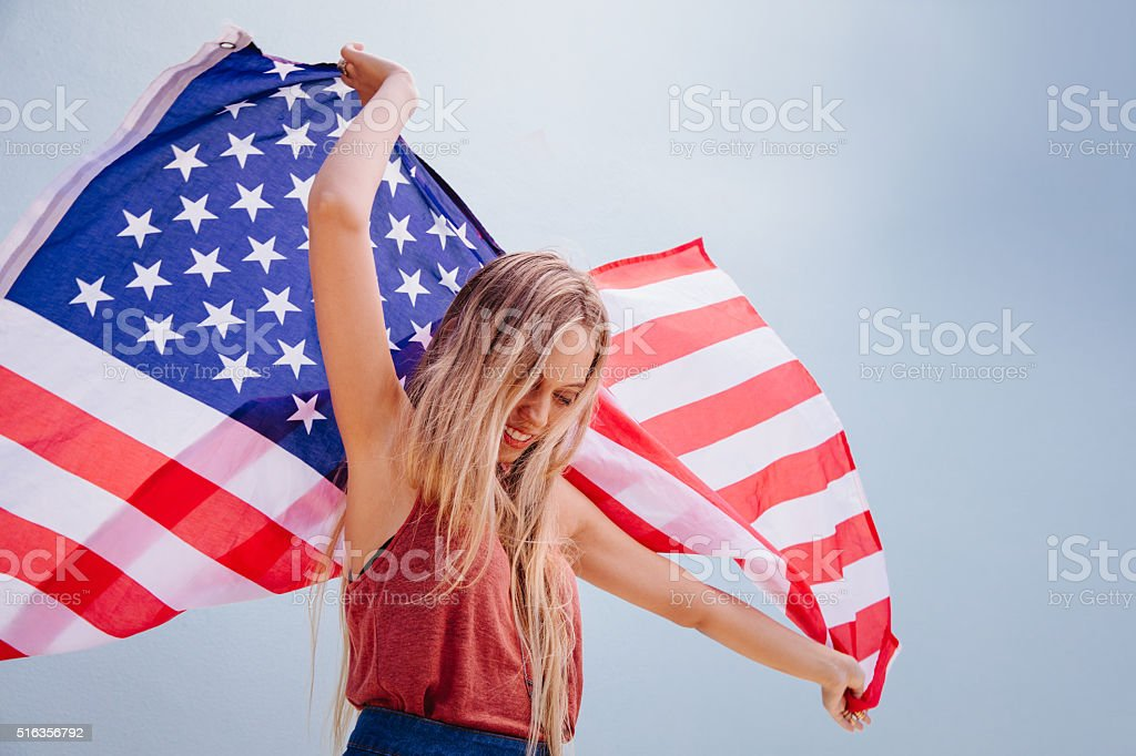 Beautiful young pretty woman with national usa flag dancing stock photo