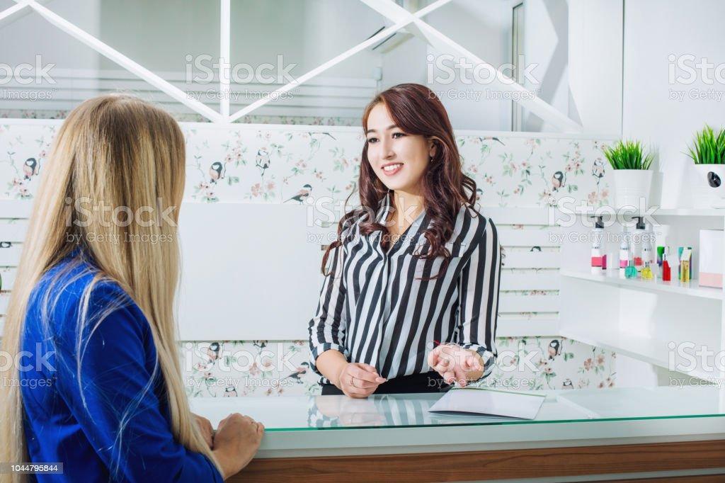 Menina linda jovem recepcionista com um sorriso na recepção atende os clientes no salão - foto de acervo
