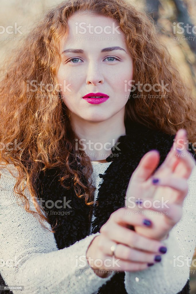 Beautiful young red-haired girl in a park stock photo