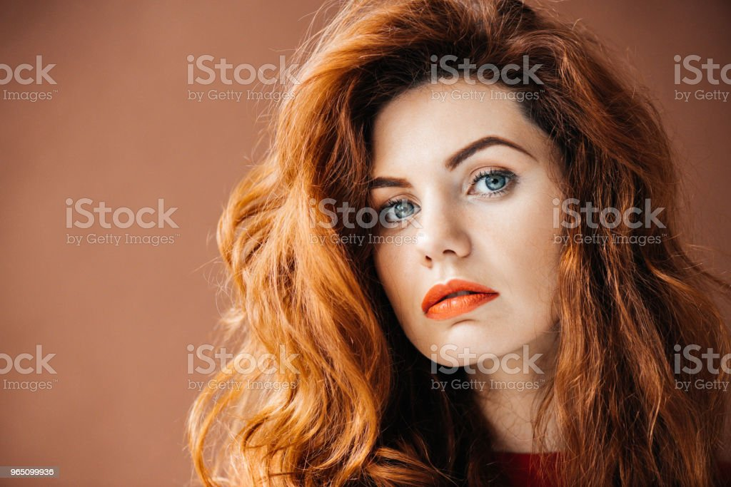 Beautiful young redhead girl isolated on brown background zbiór zdjęć royalty-free