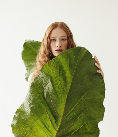 Portrait of young natural redhead woman with big leaves