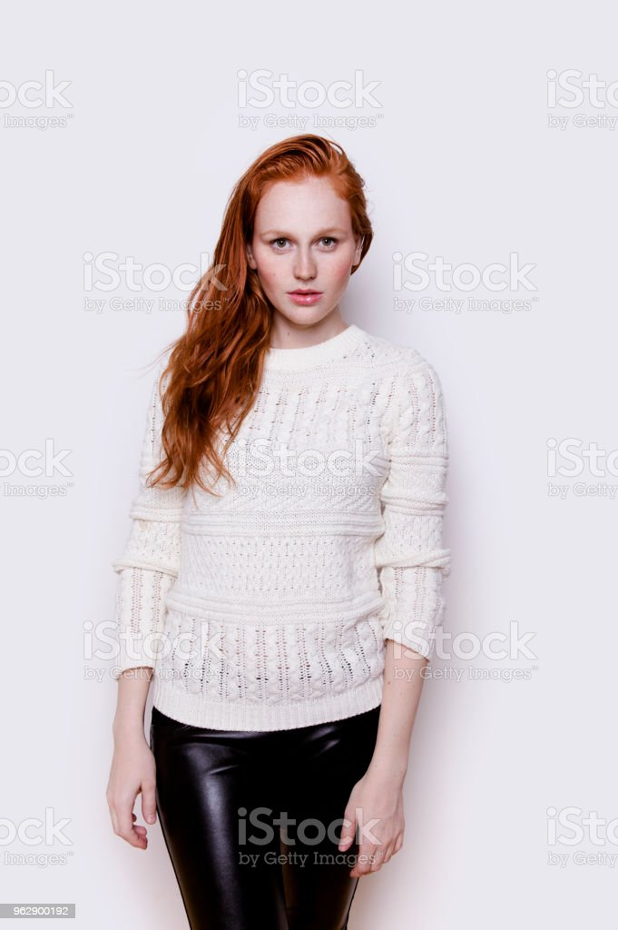 9d1a4ad0b6f72 Beautiful young redhead woman with long wavy ginger hair wearing white  sweater and black leather pants looking confident and serious - Stock image  .