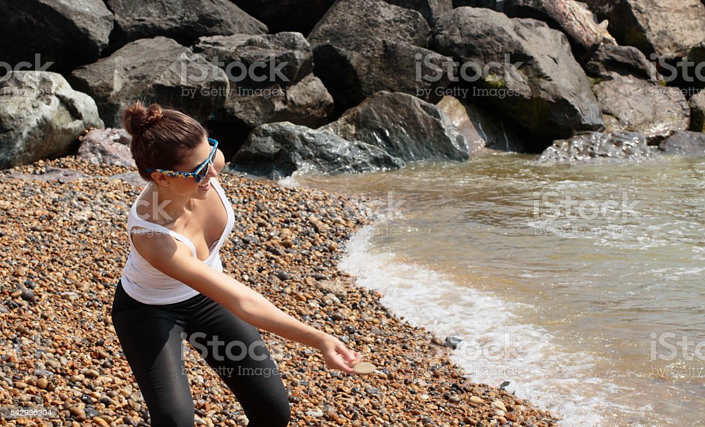 Stone skimming duckas and drakes pebble beach Russian outdoor girl stock photo