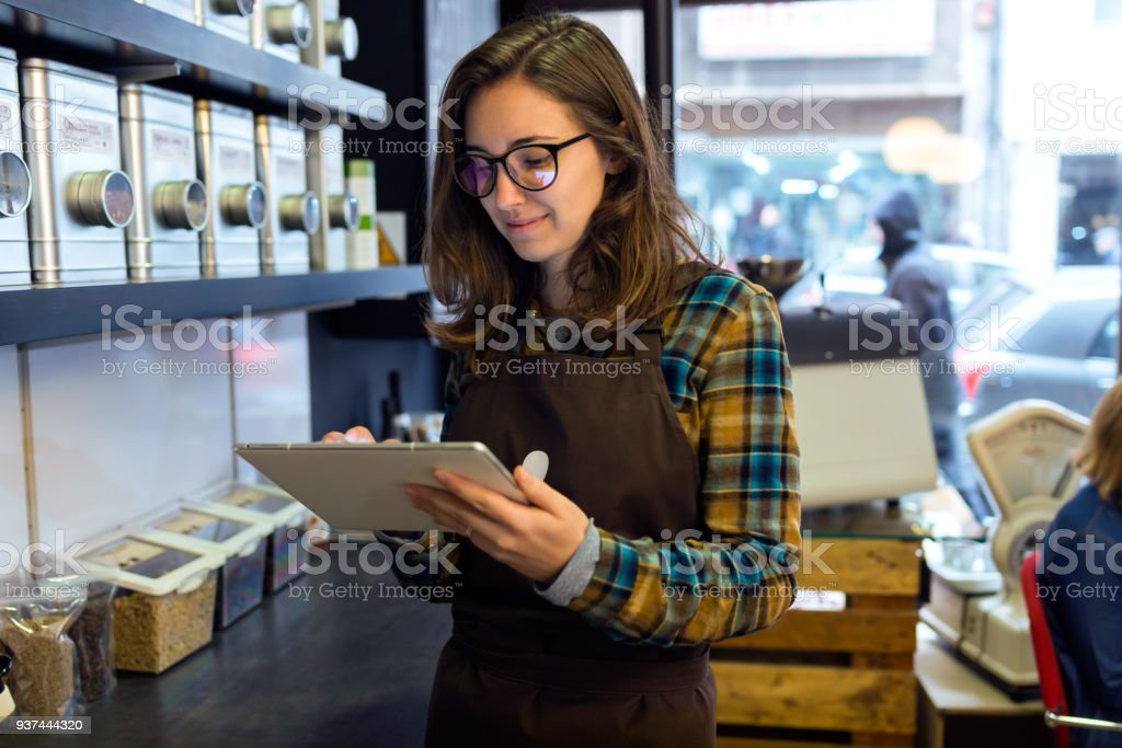 Beautiful young saleswoman doing inventory in a retail store selling coffee. stock photo