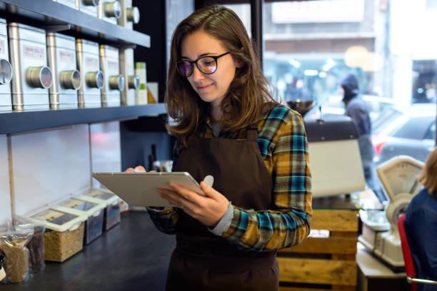 schöne junge verkäuferin inventar im ladengeschäft verkauf von kaffee zu tun. - teeladen stock-fotos und bilder