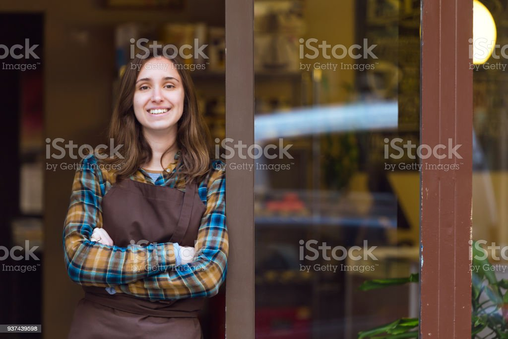 Beautiful young saleswoman looking at camera and leaning against the door frame of an organic store. stock photo