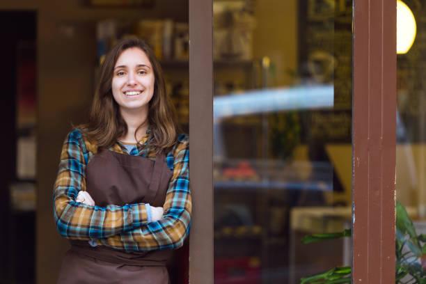 bela jovem vendedora olhando para a câmera e encostado a moldura da porta de uma loja de orgânica. - vendedor - fotografias e filmes do acervo