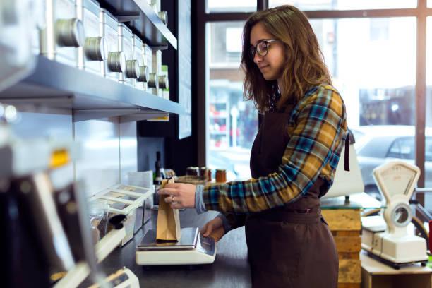 schöne junge verkäuferin mit einem gewicht von kaffeebohnen in einem ladengeschäft, verkauf von kaffee. - teeladen stock-fotos und bilder