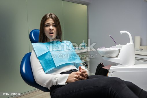 istock beautiful young scared patient woman sitting in dental chair during examination at dental office looks frightened , healthcare concept 1207033294
