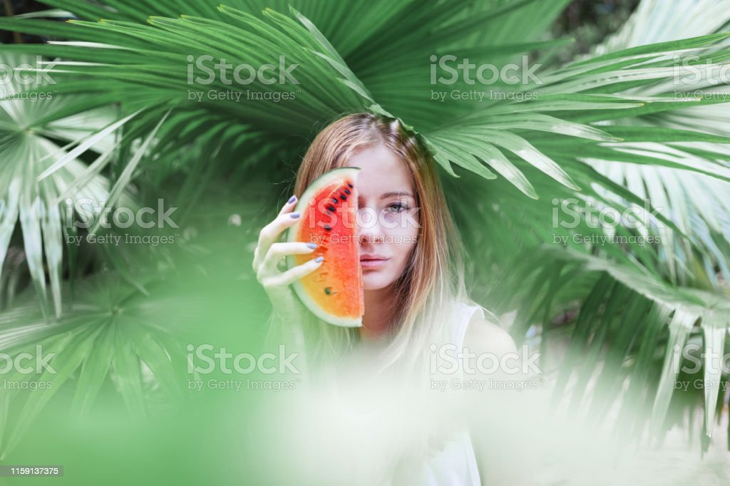 Beautiful young sensual sexy blonde with a slice of red watermelon in...