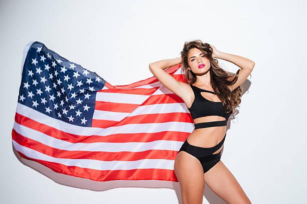 Beautiful young sexy girl posing in bikini with american flag stock photo