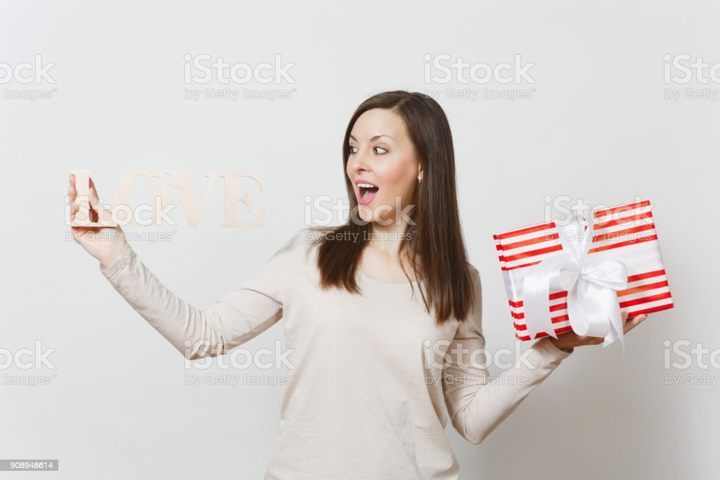 Beautiful young sexy smiling woman holding red present box with gift, wooden word love on white background. Copy space for advertisement. St. Valentine's Day or International Women's Day concept. stock photo