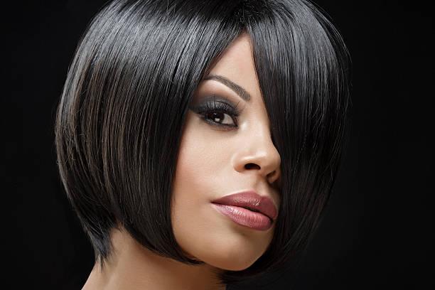 beautiful young short haired coloured female posing in studio - kurze schwarze haare stock-fotos und bilder