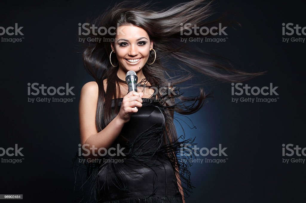 beautiful young singer on dark background royalty-free stock photo