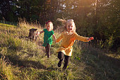 Two sisters, ages five and three, running through a meadow.