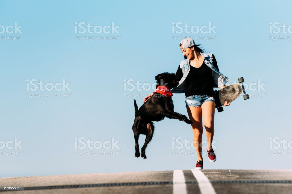 Beautiful young skater playing with her dog. royalty-free stock photo