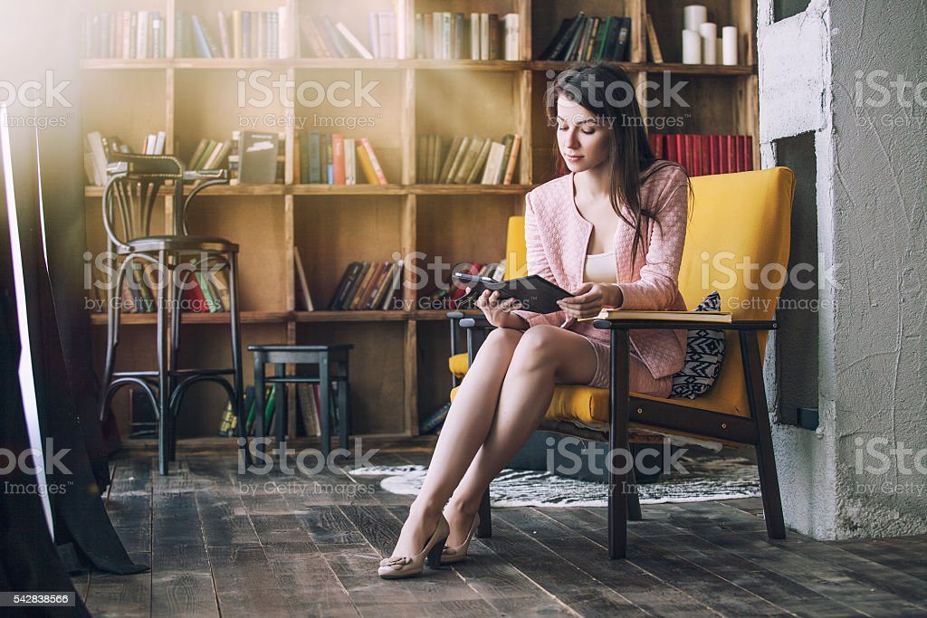 Beautiful young smart woman sits with the electronic book stock photo
