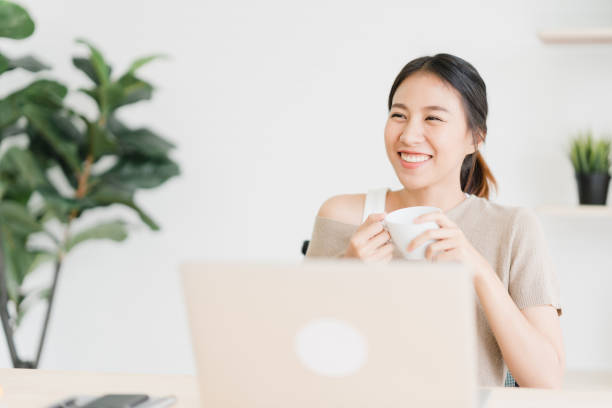 beautiful young smiling asian woman working on laptop and drinking coffee in living room at home. asia business woman working document finance and calculator in her home office. enjoying time at home. - ásia imagens e fotografias de stock