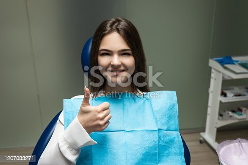 istock beautiful young smiling brunette patient woman having examination at dental office showing like sign, looking happy, healthcare concept 1207033271