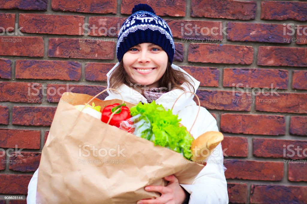 Beautiful young smiling girl with full paper food package. woman...