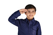 Stock image, photograph of a young Asian kid, Pranav Syal, from India in salute gesture, isolated over white color background. The boy wears a smile and a navy blue coloured Kurta, a traditional Indian or Asian dress. Jai Hind gesture.  A sweet bunny teeth smile, twinkling or twinkle eyes. Cut out, No text, Copy space. Apt for 4th, 4 th July, 15th 15 th August, 26th 26 th January, Republic Day, Independence Day greeting card.