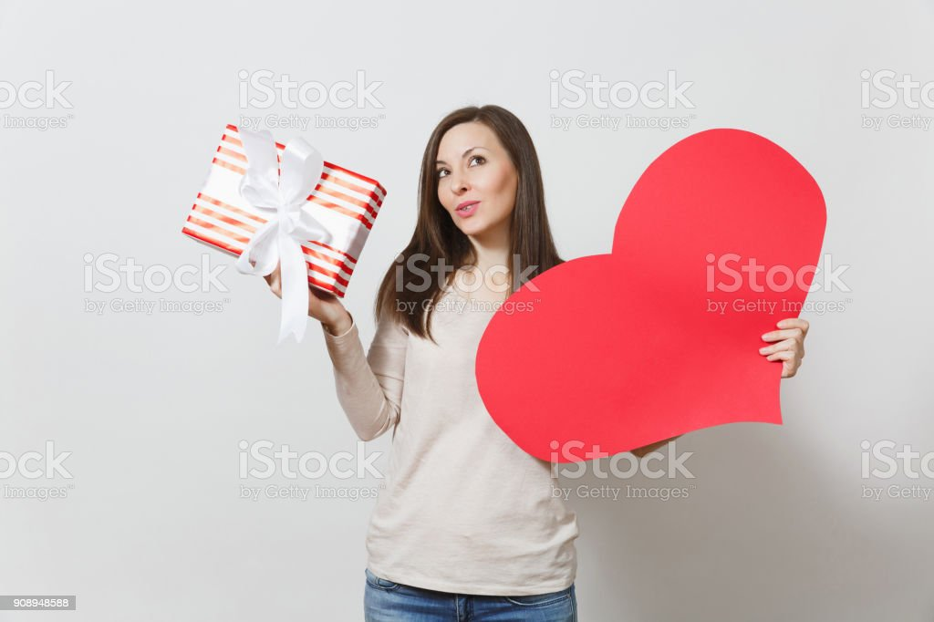 Beautiful young smiling woman holding big red heart, box with present on white background. Copy space for advertisement. With place for text. St. Valentine's Day or International Women's Day concept. stock photo
