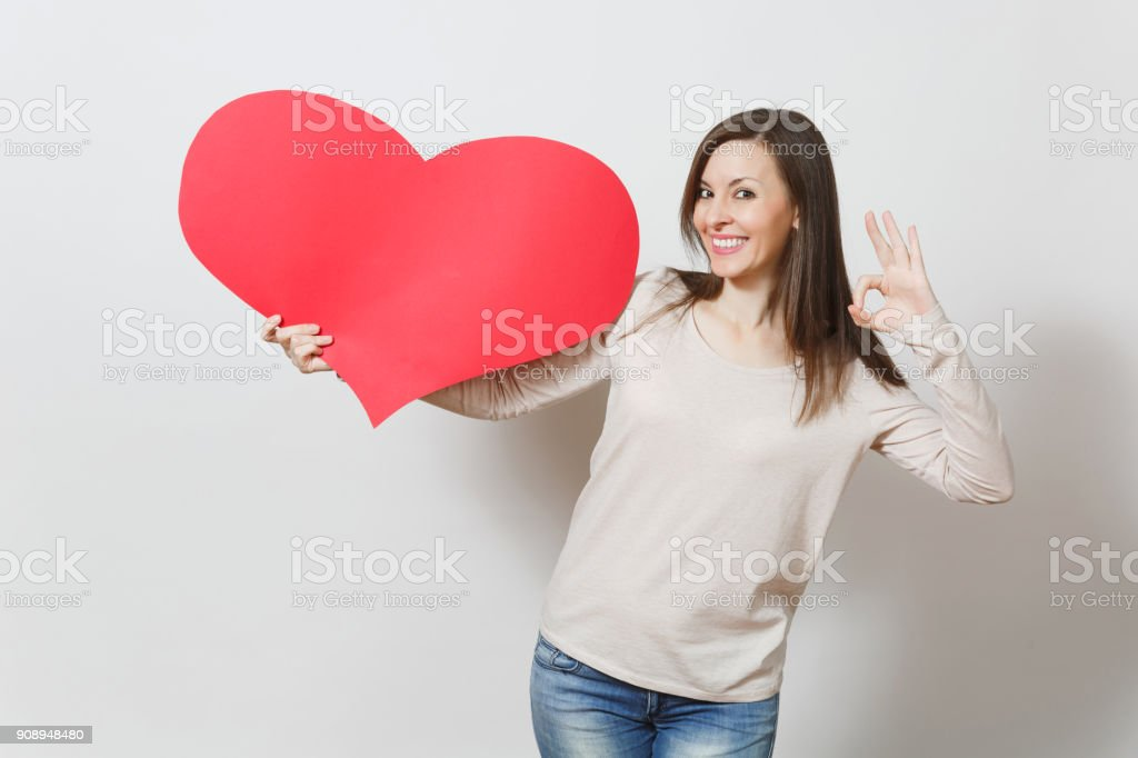 Beautiful young smiling woman holding big red heart, showing OK gesture on white background. Copy space for advertisement. With place for text. St. Valentine's Day or International Women's Day concept stock photo
