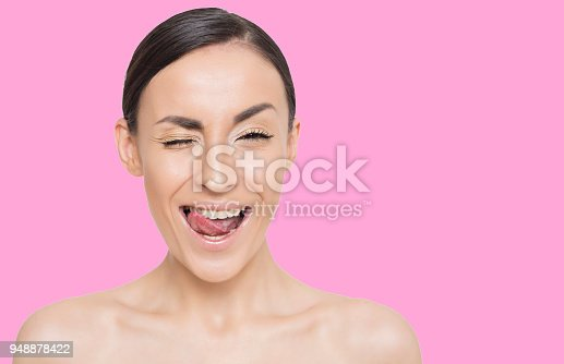 897056188 istock photo Beautiful young smiling woman on colorful background 948878422