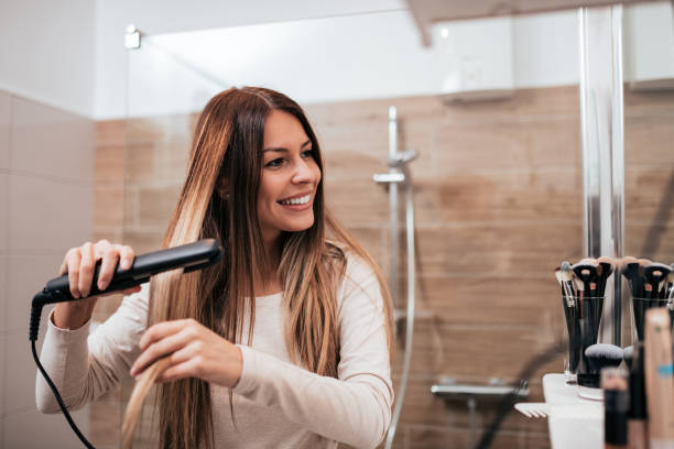 mooie jonge lachende vrouw met behulp van een hair straightener tijdens het kijken naar de spiegel in de badkamer. - bijstellen stockfoto's en -beelden