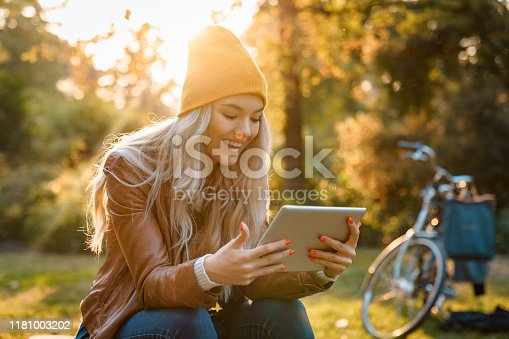 Beautiful young smiling woman using digital tablet in city park - Stock Image